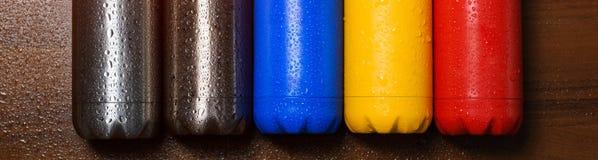 Färgrika rostfria thermo flaskor, på en trätabell som besprutas med vatten Den Matte röd flaskan, blått, guling och platina färga arkivfoton