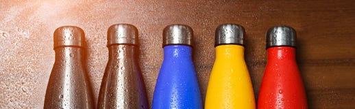Färgrika rostfria thermo flaskor, på en trätabell som besprutas med vatten Den Matte röd flaskan, blått, guling och platina färga royaltyfria foton