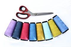 Färgrika rullar för sy tråd på vit bakgrund med sax royaltyfria foton