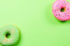 Färgrika runda donuts på grön bakgrund Lekmanna- lägenhet, bästa sikt Arkivbild