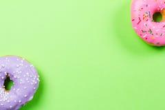 Färgrika runda donuts på grön bakgrund Lekmanna- lägenhet, bästa sikt Royaltyfria Foton