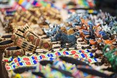 Färgrika söder - afrikansk pärlkonst i armband, noshörningen och flodhästar i öppen luft marknadsför Arkivfoto