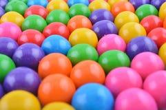 Färgrika söta gumballs väller fram arrangera i rak linje royaltyfri fotografi