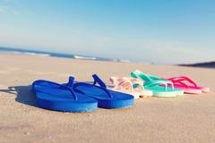 Färgrika sandaler på stranden Arkivfoto