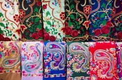 Färgrika siden- östliga turkiska sjalar på skärm arkivfoto