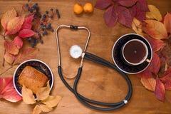 Färgrika sidor på den medicinska stetoskopet för träbakgrund royaltyfri fotografi
