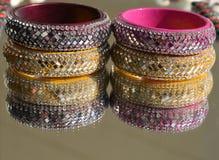 Färgrika skinande Rajasthani armringar utgjorde av exponeringsglas och lera med reflexion på spegeln i mjuk fokus Arkivbilder