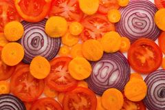 Färgrika skivor av tomater, morötter och löken Royaltyfri Bild