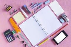 Färgrika skolatillförsel som organiseras av typ runt om anmärkningsboken som är öppen till den ordnade tomma sidan royaltyfri bild