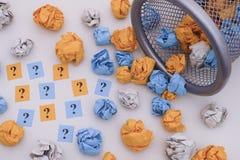 Färgrika skrynkliga pappersbollar och frågefläckar som rullar ut ur Royaltyfri Bild