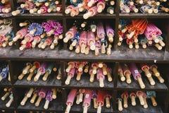 Färgrika slags solskyddparaplyer på marknaden arkivbild