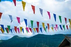 Färgrika små flaggor med molnig himmel royaltyfri fotografi