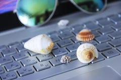 Färgrika snäckskal ligger på ett silverdatortangentbord mot bakgrunden av en skärm med en bild av havet fotografering för bildbyråer
