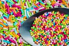 Färgrika sockerstänk i sked Royaltyfria Bilder
