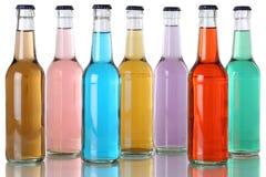 Färgrika sodavattendrinkar med cola i flaskor Fotografering för Bildbyråer