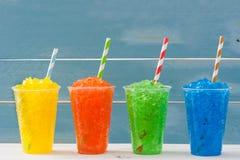 Färgrika sommarslushies på blått trä Fotografering för Bildbyråer