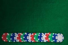 Färgrika spela chiper på grön klädd med filt bakgrund med kopieringsutrymme royaltyfri bild