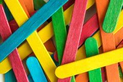 Färgrika spridda trämångfärgade isglasspinnar arkivbilder