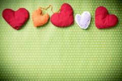 Färgrika stack hjärtor på en grön bakgrund Fotografering för Bildbyråer