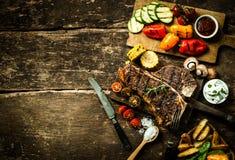 Färgrika stekgrönsaker och grillad t-ben biff Royaltyfria Bilder