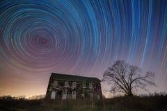 Färgrika stjärnaslingor över och övergett hus Fotografering för Bildbyråer