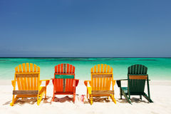 Färgrika stolar på den karibiska stranden Fotografering för Bildbyråer