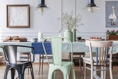 Färgrika stolar på tabellen i grå matsalinre för stuga med lampor och affischer Verkligt foto royaltyfri bild