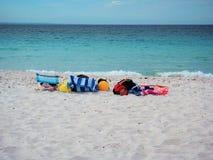 Färgrika strandhanddukar, stolar och bollar på den vita sandstranden Royaltyfri Bild