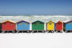 Färgrika strandkojor på den vita sandiga stranden Arkivbild