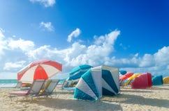 Färgrika strandparaplyer/slags solskydd och cabanas near havet Arkivfoto