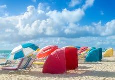 Färgrika strandparaplyer/slags solskydd och cabanas near havet Fotografering för Bildbyråer
