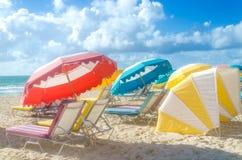 Färgrika strandparaplyer/slags solskydd och cabanas near havet Arkivbild