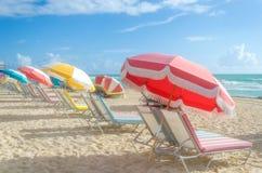 Färgrika strandparaplyer/slags solskydd och cabanas near havet Royaltyfria Bilder