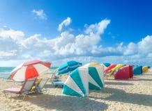 Färgrika strandparaplyer/slags solskydd och cabanas near havet Arkivfoton