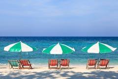 Strandstolar och paraplyer på stranden Royaltyfria Bilder