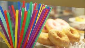 Färgrika sugrör för drinkar på bakgrunden av donuts i ett shoppafönster av en konfekt 4k ultrarapid lager videofilmer
