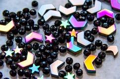 Färgrika svarta pärlor och stenar som isoleras på grå bakgrund royaltyfri bild