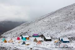 Färgrika tält täckt snö Fotografering för Bildbyråer