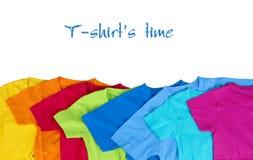 Färgrika t-skjortor på vit bakgrund Arkivbild