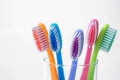 Färgrika tandborstar i exponeringsglas Arkivfoton