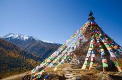 Färgrika tibetana flaggor och snöberg på Siguniang sceniskt område, Kina royaltyfri foto