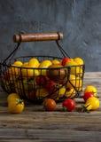 Färgrika tomater i korgen Arkivbilder
