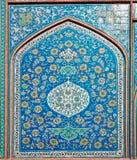 Färgrika träd- och blommamodeller på den gamla tegelplattan av den historiska väggen av en iransk byggnad i Isfahan, Iran Arkivbild