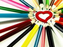 Färgrika träfärgpennor och röd hjärta Arkivfoton