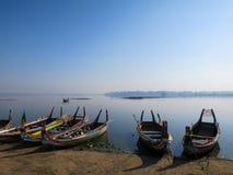 Färgrika träfartyg på banken av den fridsamma lugnt vattensjön med Arkivfoto