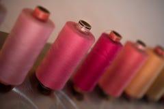 Färgrika trådrullar som används i tyg- och textilbransch Fotografering för Bildbyråer
