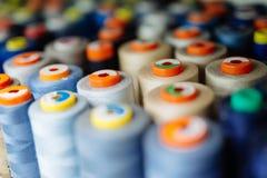 Färgrika trådrullar som används i tygbransch Arkivbilder