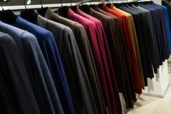 Färgrika tröjor som hänger i kläddetaljist arkivfoto