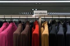 Färgrika tröjor som hänger i kläddetaljist Nytt samlingsID-Märke Royaltyfri Foto