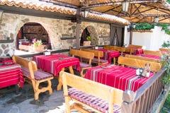 Färgrika traditionella röda borddukar på trätabeller och bänkar, gammal bulgarisk restaurang Royaltyfri Foto